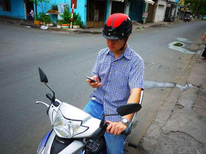 やる気無さげに携帯をいじりながらバイクに乗るLam君。