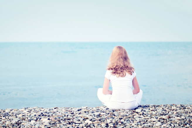 sad lonely  young beautiful woman sitting back on beach